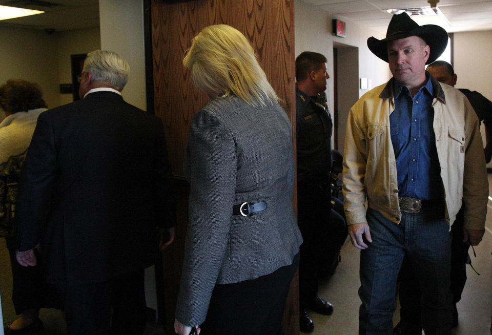 Photo -   Country music star Garth Brooks, right, walks into a Rogers County Courthouse courtroom in Tulsa, Okla. with his wife Trisha Yearwood, center, and attorney John Hickey, on Tuesday, Jan. 17, 2012. Brooks appeared before the jurors who will hear his claim that an Oklahoma hospital refused to name a building for his late mother after he gave it $500,000. (AP Photo/The Tulsa World, Cory Young) ONLINE OUT; TV OUT; TULSA OUT