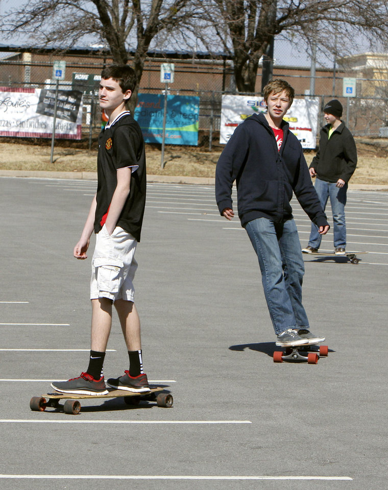 Below: Brothers Chris Taylor, left, Thomas  Taylor and Spencer  Taylor, use the wind  and sloped parking lot Monday to enjoy some skateboarding at Hafer Park in Edmond.  Photo By Paul Hellstern,  The Oklahoman