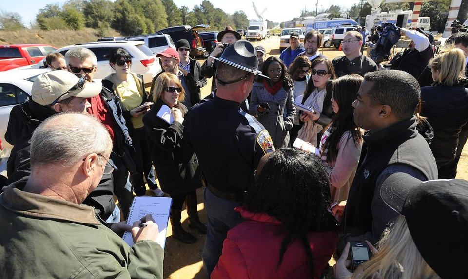 Photo - Alabama state trooper Kevin Cook, center right, is surrounded by members of the media following a news conference, Saturday, Feb. 2, 2013, in Midland City, Ala. Authorities said they still have an open line of communication with an Alabama man accused of abducting a 5-year-old child and holding him hostage in a bunker since Tuesday, Jan. 29. Sheriff Wally Olson said Saturday that Jimmy Lee Dykes has told them that he has blankets and an electric heater in the bunker. (AP Photo/al.com, Joe Songer) MAGS OUT.