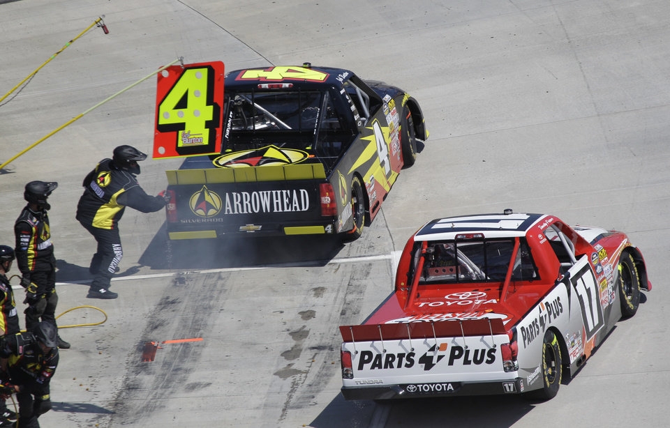 Driver Jeb Burton (4) beats Timothy Peters (17) out of the pits during the Kroger 250 NASCAR Truck series auto race at Martinsville Speedway, Saturday, April 6, 2013, in Martinsville, Va. (AP Photo/Steve Helber)