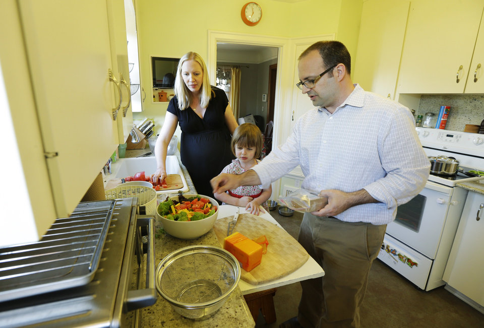 Photo - In this July 2, 2014 photo, Ryan Carson, right, cooks dinner with his wife, Jenny Roraback-Carson, left, and their daughter Clara, 3, at their home in Seattle. The Carsons are one of many would-be home sellers across the country who have mortgage rates so low, it doesn't make financial sense to sell their homes, even if they need more space, a trend which limits the supply of homes and can contribute to slower home sales. (AP Photo/Ted S. Warren)