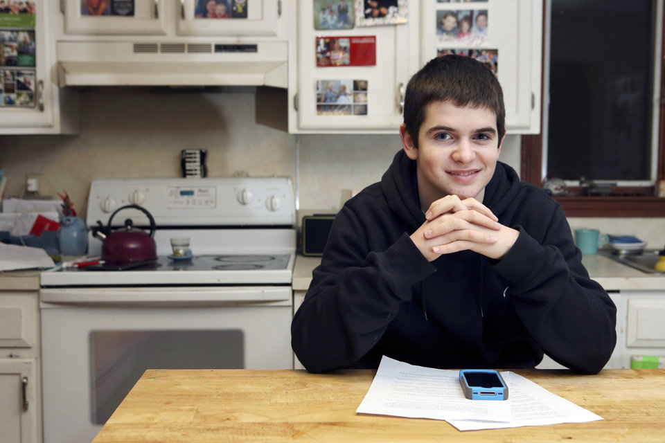 In this Jan. 4, 2013, photo, Gregory Hofmann, 13, poses with his Apple iPhone and a signed contract at his home in Sandwich, Mass. Hofmann's mother Janell drafted the contract which outlines conditions for his use of the phone. (AP Photo/Michael Dwyer)
