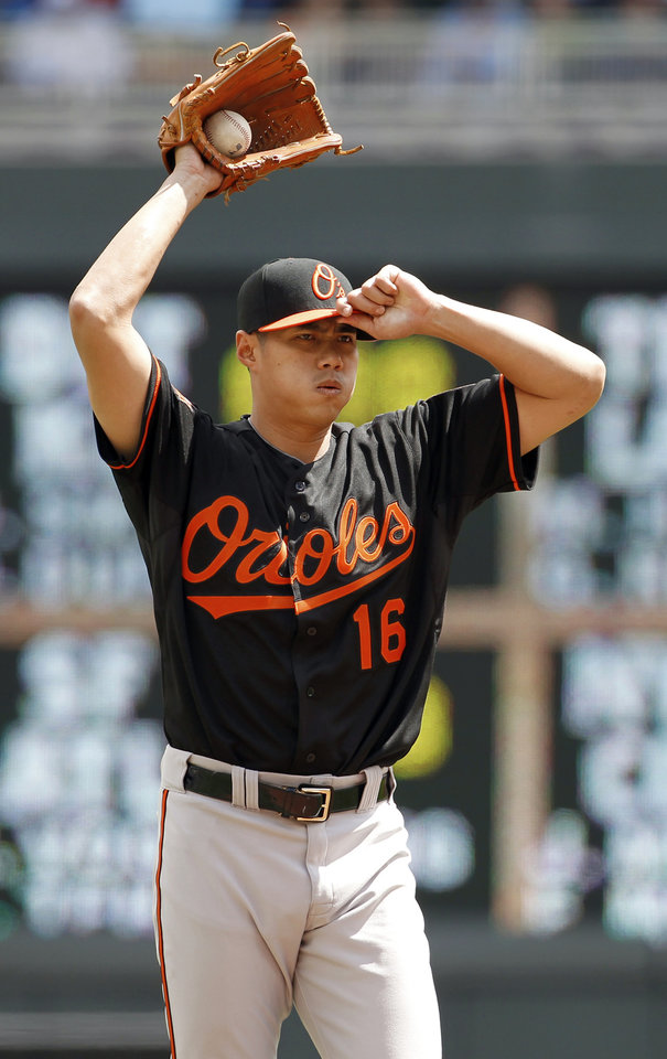 Photo - Baltimore Orioles starting pitcher Wei-Yin Chen adjusts his cap after giving up a single to Minnesota Twins' Joe Mauer  during the first inning of a baseball game in Minneapolis, Saturday, May 3, 2014. The Twins won 6-1. (AP Photo/Ann Heisenfelt)