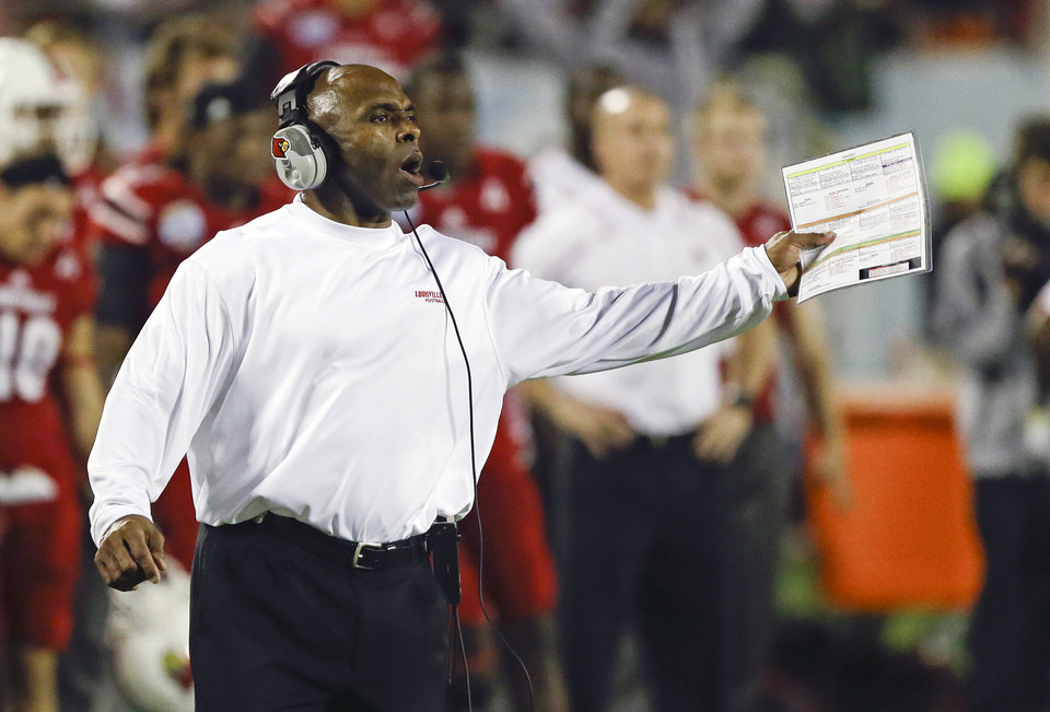 Photo - FILE - In this Dec. 28, 2013, file photo, Louisville head coach Charlie Strong calls out to players on the field during the second half of the Russell Athletic Bowl NCAA college football game against Miami in Orlando, Fla. New Texas football coach Strong says he is excited to lead one of the premier programs in the country, calling the Longhorns job a dream. In a statement released by the school formally announcing the hire Sunday, Jan. 5, 2014, Strong called Texas a special program because of its history, tradition and pride. (AP Photo/John Raoux, File)