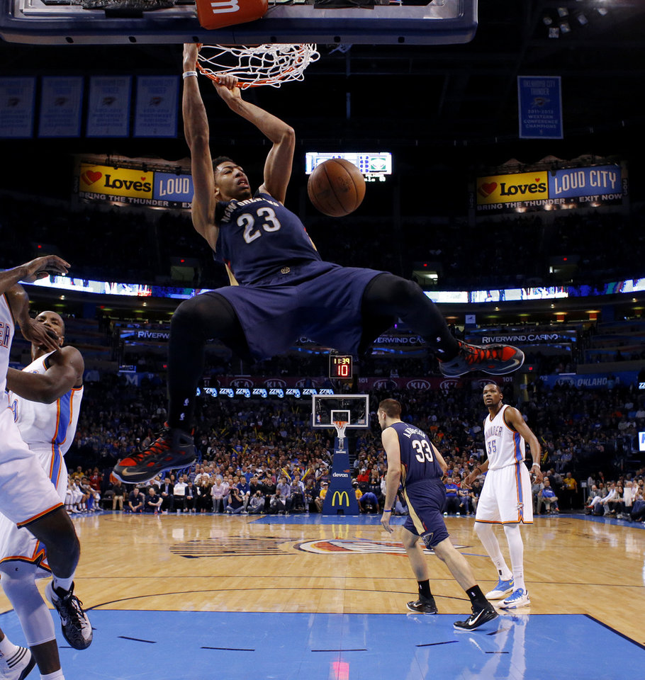 Photo - New Orleans' Anthony Davis (23) dunks the ball as Oklahoma City's Kevin Durant (35) watches during an NBA game between the Oklahoma City Thunder and the New Orleans Pelicans at Chesapeake Energy Arena on Friday, Feb. 6, 2015. Photo by Bryan Terry, The Oklahoman