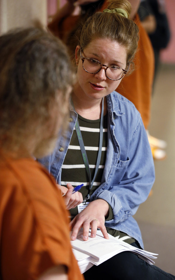 Photo -  Outreach worker Abigail Otto speaks with inmates as she works with District Judge Cindy Truong to reduce the Oklahoma County jail population. [Photo by Steve Sisney, The Oklahoman]
