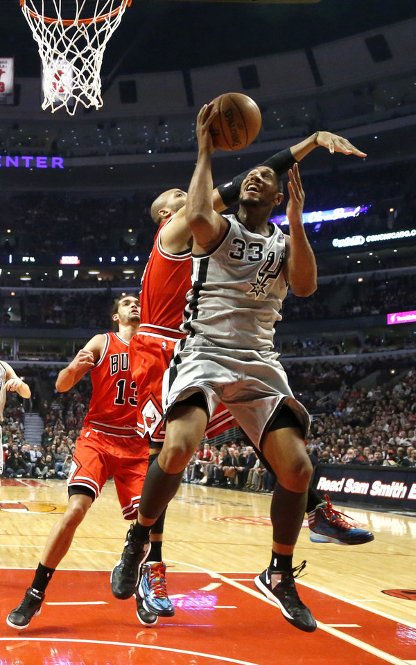 San Antonio Spurs center Boris Diaw (33) shoots past Chicago Bulls forward Taj Gibson and center Joakim Noah (13) during the first half of an NBA basketball game, Monday, Feb. 11, 2013, in Chicago. (AP Photo/Charles Rex Arbogast)