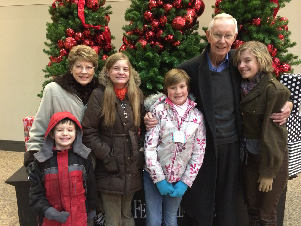 Photo -       Marilyn Kratz poses with her husband, Bud, and their grandchildren at the 2013 Festival of Trees.