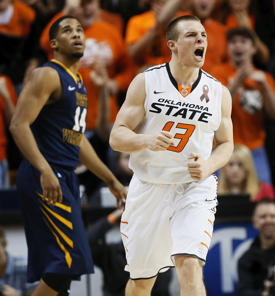 Oklahoma State's Phil Forte (13) reacts in front of West Virginia's Gary Browne (14) after hitting a 3-point shot during an NCAA college basketball game in Stillwater, Okla., Saturday, Jan. 26, 2013. (AP Photo/The Oklahoman, Nate Billings)