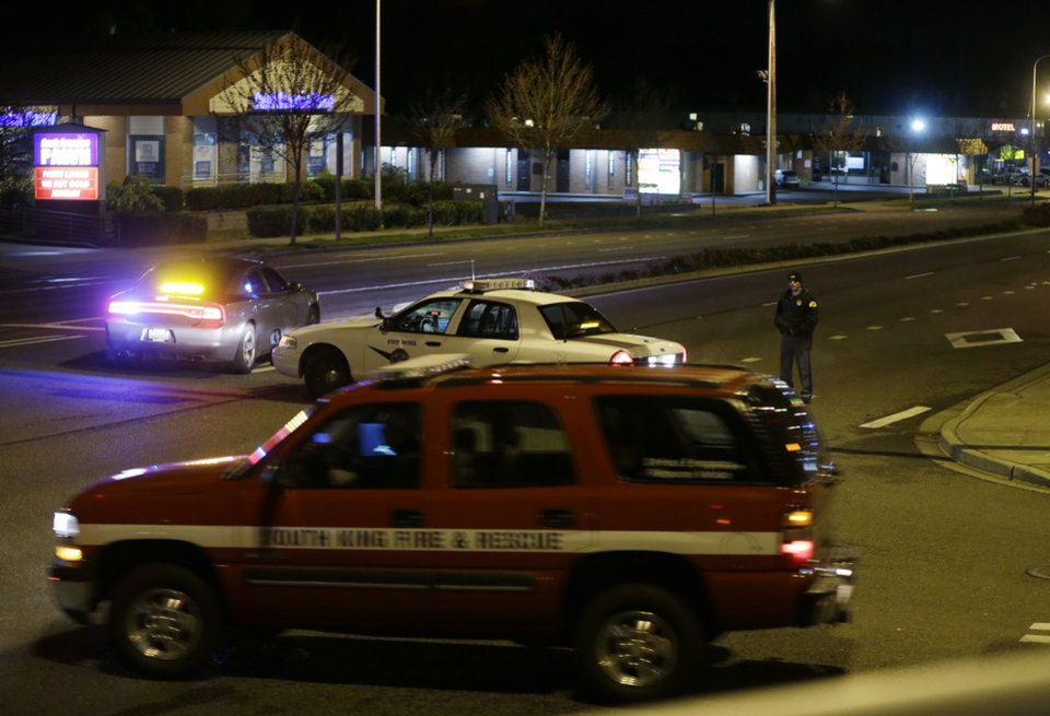 Photo - Police and fire vehicles are seen several blocks from the scene of an overnight shooting that police said left five people dead, Monday, April 22, 2013, at an apartment complex in Federal Way, Wash. (AP Photo/Ted S. Warren)