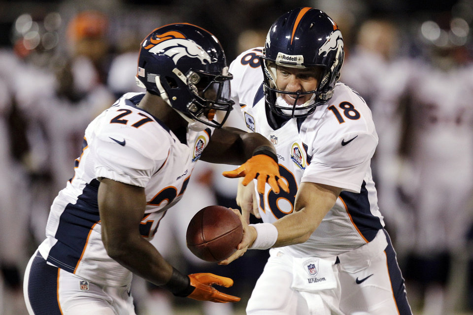 Photo - Denver Broncos quarterback Peyton Manning (18) hands off to running back Knowshon Moreno during the first quarter of an NFL football game against the Oakland Raiders in Oakland, Calif., Thursday, Dec. 6, 2012. (AP Photo/Ben Margot)