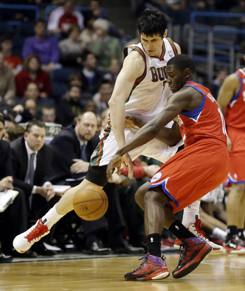 Photo - Milwaukee Bucks' Ersan Ilyasova, left, steals the ball from Philadelphia 76ers' Jrue Holiday, right, in the second half of an NBA basketball game, Tuesday, Jan. 22, 2013, in Milwaukee. (AP Photo/Jeffrey Phelps)