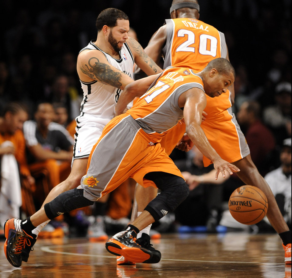 Phoenix Suns' Sebastian Telfair (31) drives the ball past Brooklyn Nets' Deron Williams (8) in the first half of an NBA basketball game on Friday, Jan., 11, 2013 at Barclays Center in New York. (AP Photo/Kathy Kmonicek)