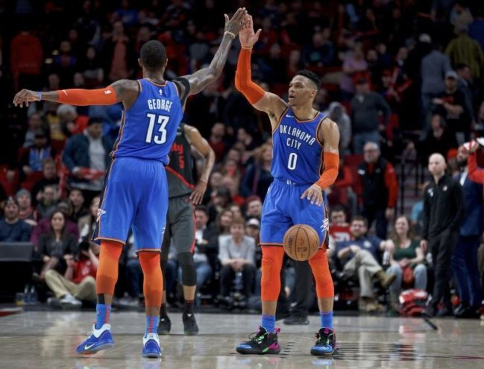 Photo -  Thunder guard Russell Westbrook, right, and forward Paul George high-five at the end of a 129-121 overtime win in Portland on Thursday. [AP Photo/Craig Mitchelldyer]