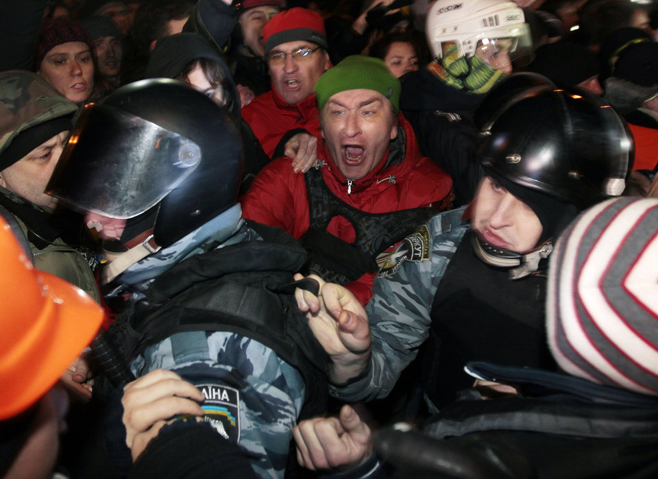 Photo - Pro-European Union activists block riot police near a Svyatoshin police station in Kiev, Ukraine, Saturday, Jan. 11, 2014. Kiev has been the scene of massive pro-European protests for more than a month, triggered by Ukrainian President Viktor Yanukovych's decision to ditch a key deal with the European Union in favor of building stronger ties with Russia. (AP Photo/Sergei Chuzavkov)