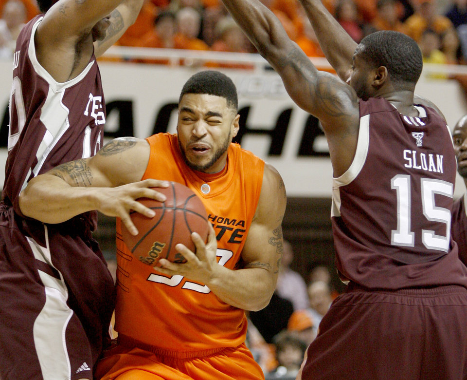 Photo - OSU's Marshall Moses goes between Texas A&M's David Loubeau, left, and Donald Sloan during an NCAA college basketball game between the Oklahoma State University and Texas A&M at Gallagher-Iba Arena in Stillwater, Okla., Wednesday, January 27, 2010. Photo by Bryan Terry, The Oklahoman