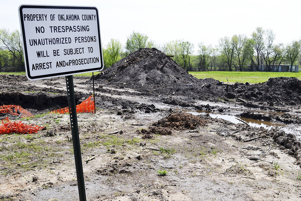 Photo - Mud and water cover one of several lots in Crutcho on Wednesday. The vacant lot is among several dozen in the neighborhood bought and razed by Oklahoma County as part of a long-term flood remediation project. Photo By Zeke Campfield, The Oklahoman
