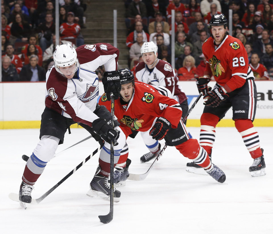 Photo - Colorado Avalanche defenseman Tyson Barrie (4) handles the puck in front of the Chicago Blackhawks's goal as defenseman Niklas Hjalmarsson (4) and Bryan Bickell (29) defend during the first period of an NHL hockey game Tuesday, March 4, 2014, in Chicago. Also watching the play is Coilorado's Cody McLeod (55).  (AP Photo/Charles Rex Arbogast)