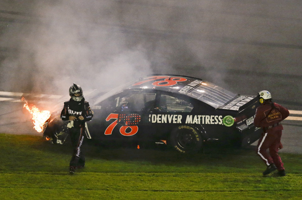Photo - Martin Truex Jr., left, walks away from his car after he was involved in a multi-car crash on the last lap of the second of two NASCAR Sprint Cup qualifying auto races at Daytona International Speedway in Daytona Beach, Fla., Thursday, Feb. 20, 2014. (AP Photo/John Raoux)
