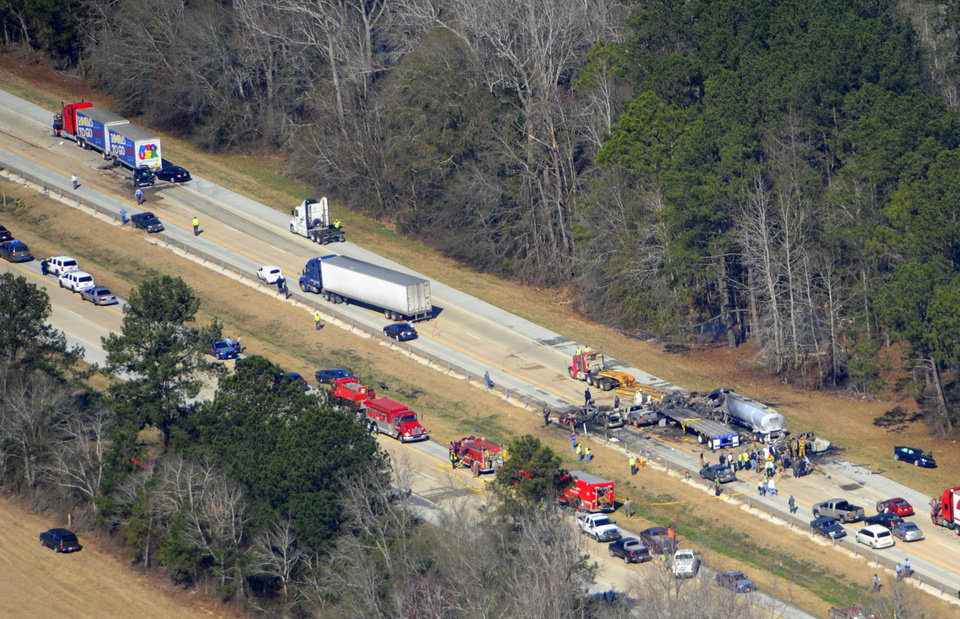 Photo - Emergency workers and firemen are at he scene of a pile up on Interstate 16 near Jeffersonville, Ga., Wednesday Feb. 6, 2013.   More than two dozen vehicles collided in a fiery pileup on the foggy Georgia interstate on Wednesday morning, killing at least three people and leaving several others hurt, officials said.  (AP Photo/The Macon Telegraph, Woody Marshall)
