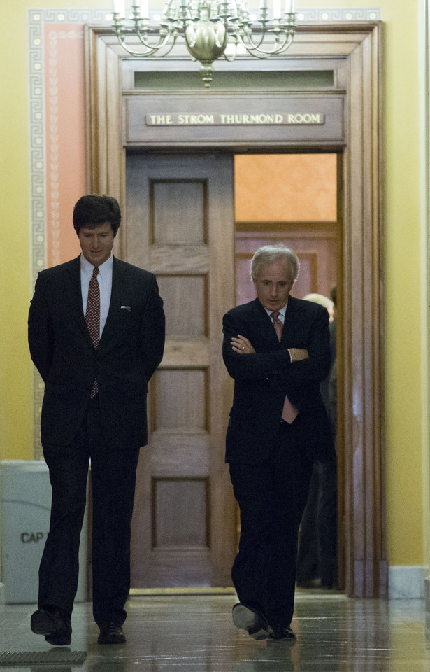 Photo - Sen. Bob Corker, R-Tenn., right, departs the Strom Thurmond room, with an aide, after a Senate Republican caucus meeting about the fiscal cliff, on Capitol Hill Monday, Dec. 31, 2012 in Washington. (AP Photo/Alex Brandon)