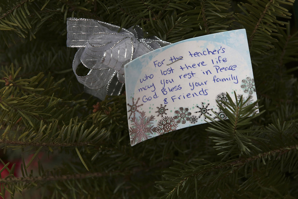 Photo - A note is left at one of the makeshift memorials for the Sandy Hook Elementary School shooting victims, Monday, Dec. 17, 2012 in Newtown, Conn. Authorities say gunman Adam Lanza killed his mother at their home on Friday and then opened fire inside the Sandy Hook Elementary School in Newtown, killing 26 people, including 20 children, before taking his own life. (AP Photo/Mary Altaffer) ORG XMIT: CTMA117