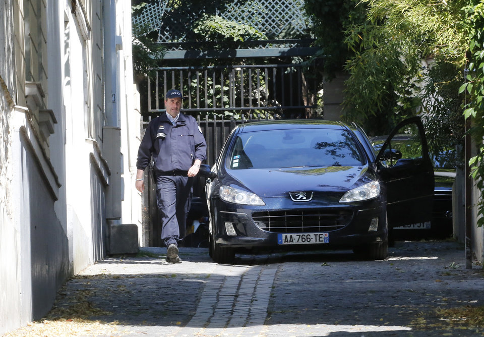 Photo - A police officer walks outside former French President Nicolas Sarkozy's house in Paris, Wednesday, July 2, 2014. Sarkozy, his lawyer and a magistrate are facing preliminary charges in a corruption investigation linked to allegations that he took 50 million euros ($67 million) in illegal campaign funds from Libya's Moammar Gadhafi, after a night of questioning by judicial officials. (AP Photo/Jacques Brinon)