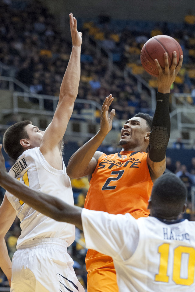 Photo - Oklahoma State's Le'Bryan Nash, left, looks to shoot over West Virginia's Nathan Adrian during the first half of an NCAA college basketball game Saturday, Jan. 11, 2014, in Morgantown, W.Va. (AP Photo/Andrew Ferguson)