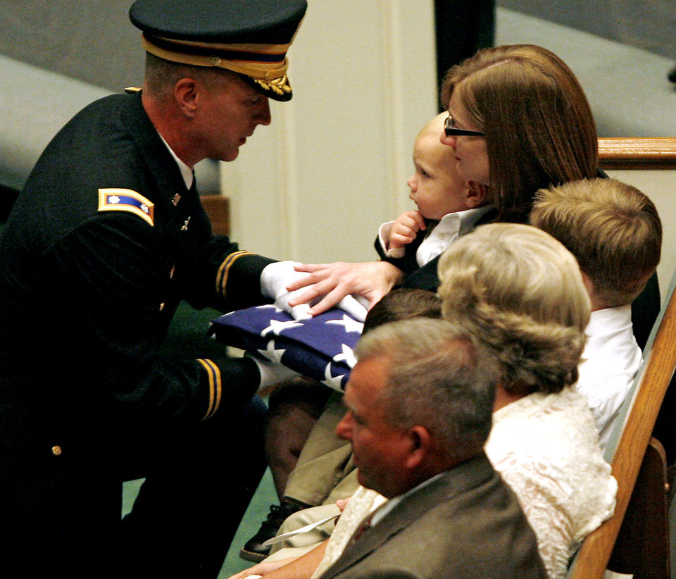 A member of the honor guard gives a flag to Jennifer Rudolf as she holds her youngest son, Nate, 21 months, during the funeral for her husband, Chief Warrant Officer Brady Rudolf, at Southern Hills Baptist Church in Oklahoma City on Sunday Sept. 28, 2008. By John Clanton, The Oklahoman