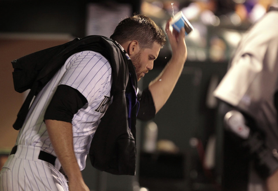 Photo - Colorado Rockies relief pitcher Adam Ottavino throws a cup of water in the dugout after leaving the baseball game against the Chicago Cubs in the 11th inning in Denver on Tuesday, Aug. 5, 2014. (AP Photo/Joe Mahoney)