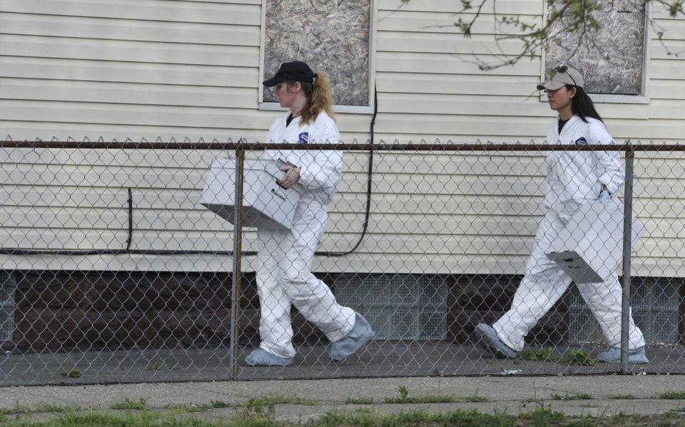Photo - Members of the FBI evidence response team carries out a bag after searching a house near the home where three women were held Wednesday, May 8, 2013, in Cleveland. Amanda Berry, 27, Michelle Knight, 32, and Gina DeJesus, about 23, had apparently been held captive in the house nearby since their teens or early 20s, police said. (AP Photo/Roadell Hickman)