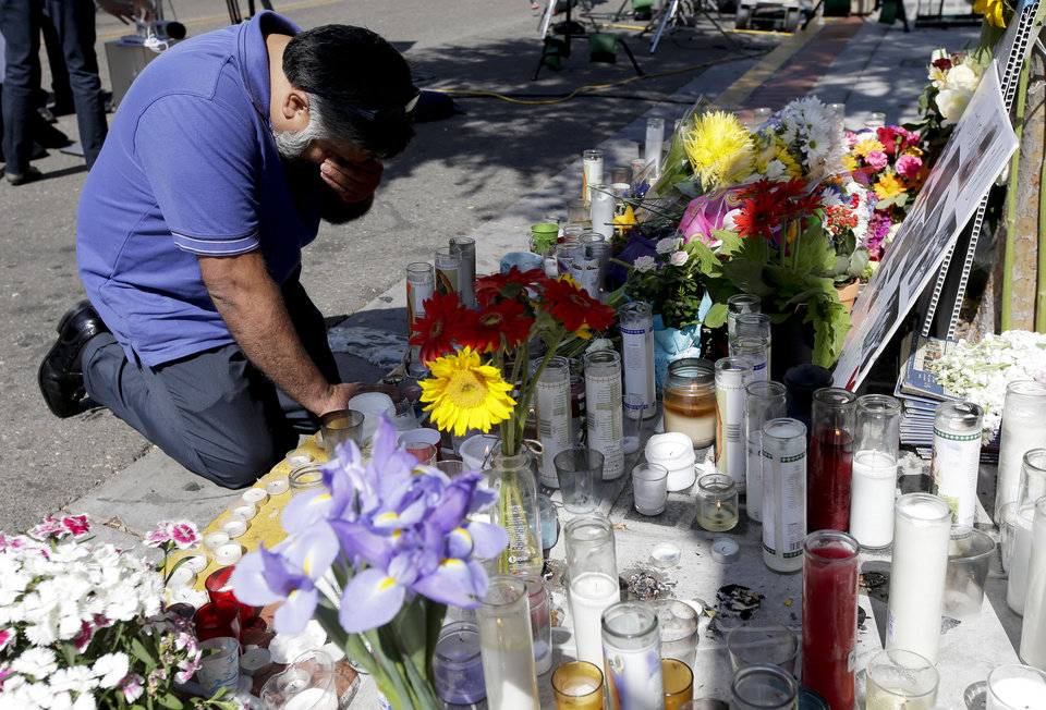 Photo - Jose Cardoso pays his respects at a makeshift memorial in front of the IV Deli Mart, where part of Friday night's mass shooting took place by a drive-by shooter Sunday, May 25, 2014, in the Isla Vista area near Goleta, Calif. Sheriff's officials said Elliot Rodger, 22, went on a rampage near the University of California, Santa Barbara, stabbing three people to death at his apartment before shooting and killing three more in a crime spree through a nearby neighborhood. (AP Photo/Chris Carlson)