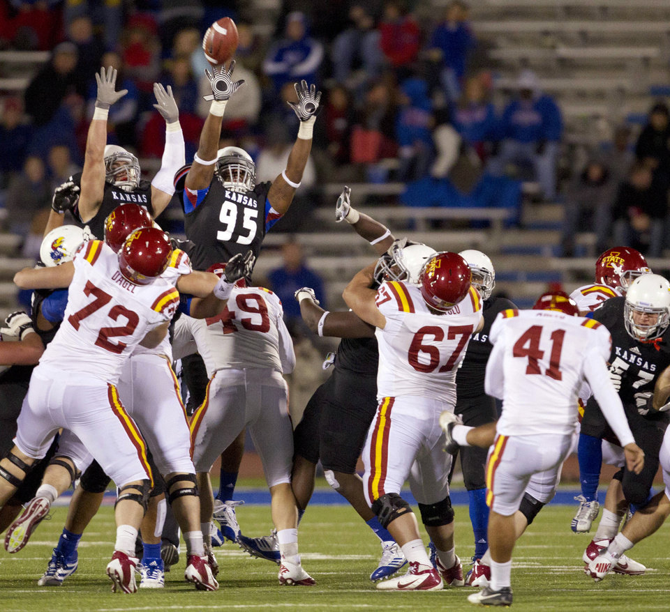 Iowa State kicker Edwin Arceo (41) boots a field goal over Kansas defensive lineman Josh Williams (95) and linebacker Ben Heeney (31) during the second half of an NCAA college football game in Lawrence, Kan., Saturday, Nov. 17, 2012. (AP Photo/Orlin Wagner)