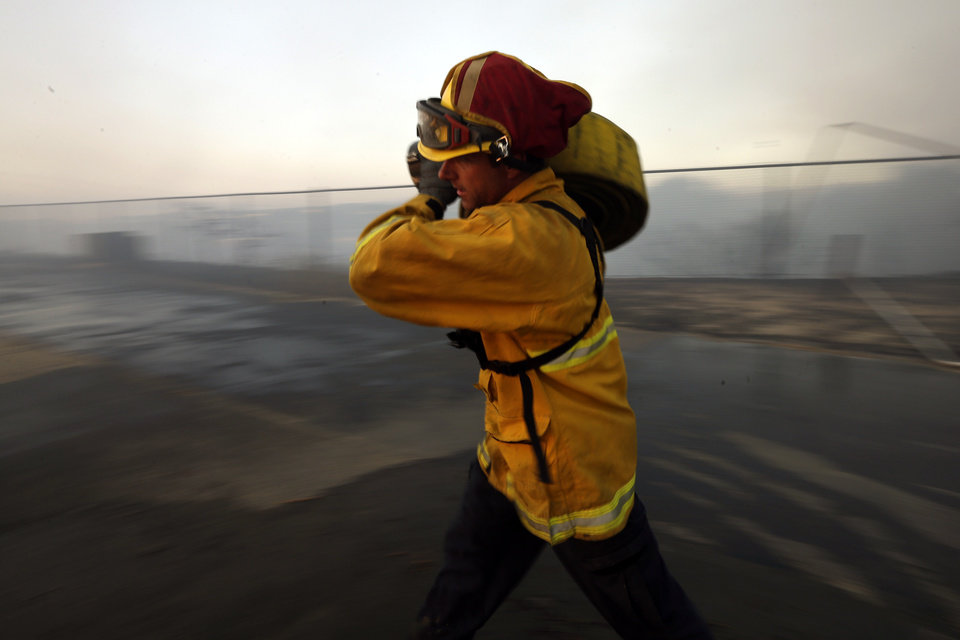 Photo - A Del Mar firefighter rolls up hose after a day fighting wildfires Wednesday, May 14, 2014, in Carlsbad, Calif. Flames engulfed suburban homes and shot up along canyon ridges in one of the worst of several blazes that broke out Wednesday in Southern California during a second day of a sweltering heat wave, taxing fire crews who fear the scattered fires mark only the beginning of a long wildfire season. (AP Photo)