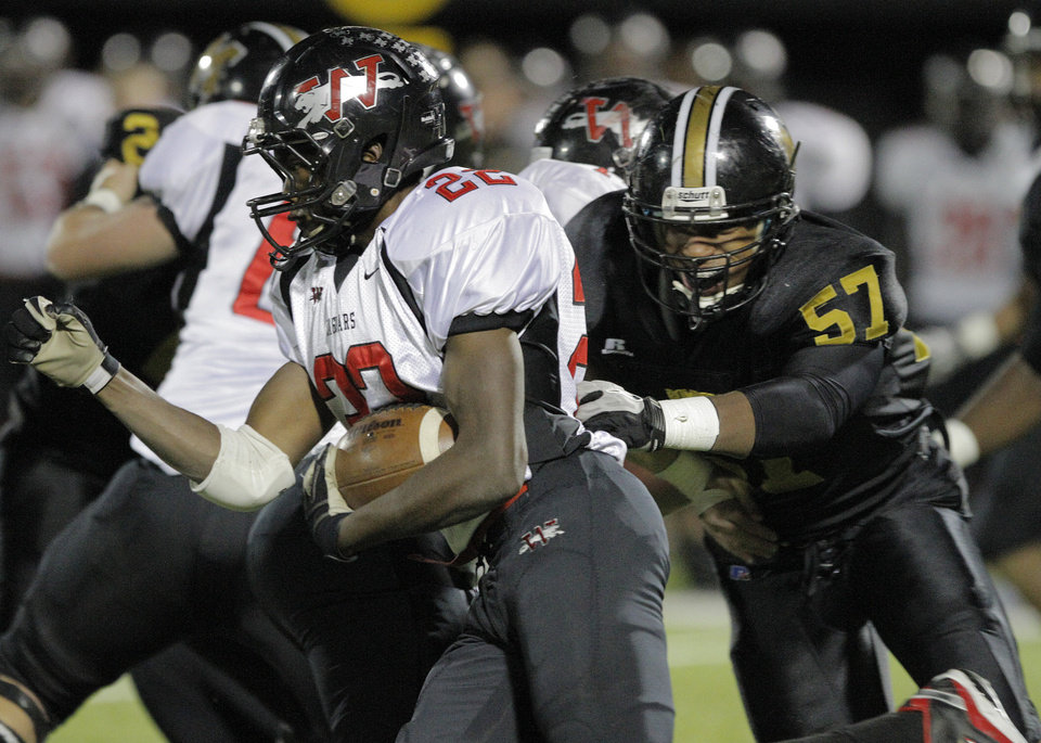 Photo - Westmoore's Austin Richards (22) runs out of reach of Midwest City's Chris Shannon (57) during a high school football game between Midwest City and Westmoore in Midwest City, Friday, Nov. 11, 2011.  Photo by Garett Fisbeck, for The Oklahoman