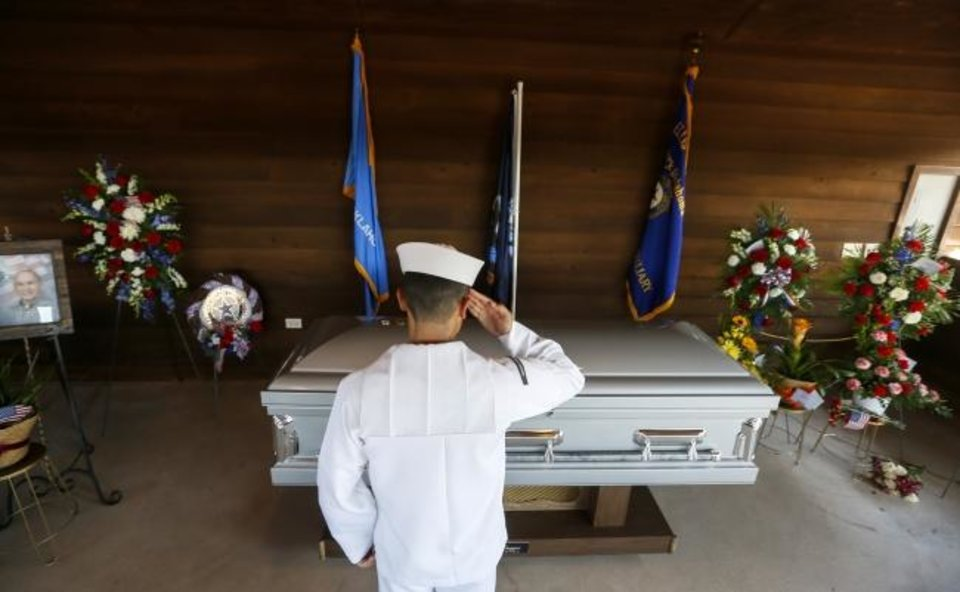 Photo -  A Navy sailor salutes the casket of Herman White at the end the funeral service for the World War II veteran at Grace Hill Cemetery in Perry, Okla., Wednesday, Sept. 4, 2019. Hundreds of people attended Navy Seaman 2nd Class White's funeral after learning that he had no surviving family members to be there. [Nate Billings/The Oklahoman]