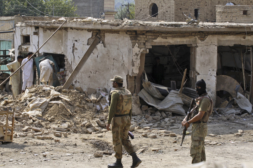 Photo -   Pakistani men, left, check the damage caused by a car bomb explosion, while army soldiers gather at the site in the Pakistani town of Darra Adam Khel in the troubled Khyber Pakhtunkhwa province bordering Afghanistan, Saturday, Oct. 13, 2012. A powerful car bomb went off outside the offices of pro-government tribal elders in northwestern Pakistan on Saturday, killing several people, police said. (AP Photo/Mohammad Sajjad)