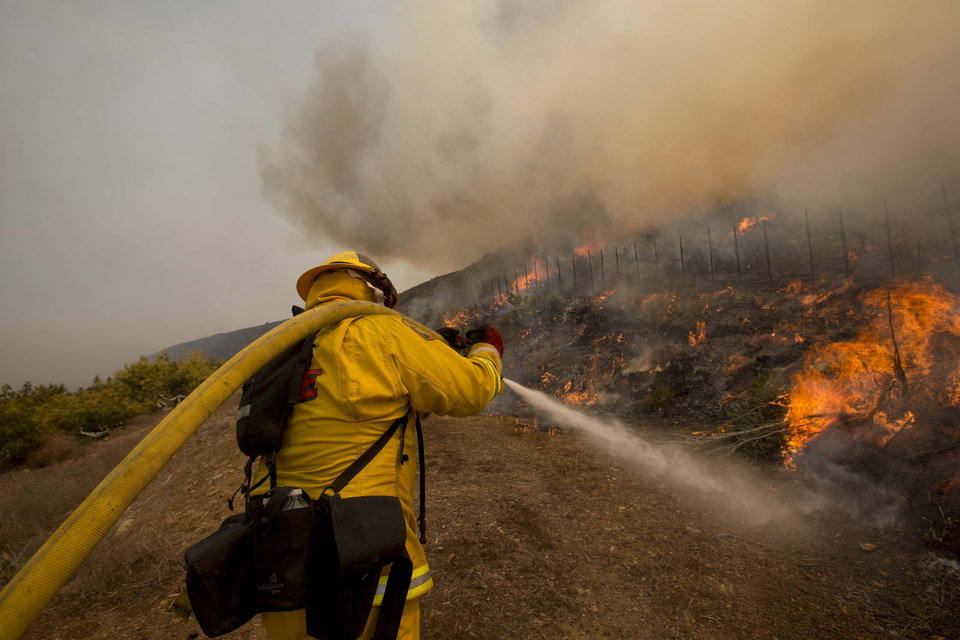A firefighter extinguishes the wildfire along a hillside in Point Mugu, Calif., Friday, May 3, 2013. Firefighters got a break as gusty winds turned into breezes, but temperatures remained high and humidity levels are expected to soar as cool air moved in from the ocean and the Santa Ana winds retreated. (AP Photo/Ringo H.W. Chiu) ORG XMIT: CARC121