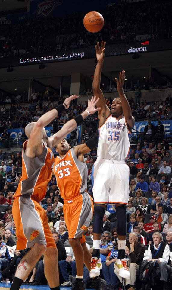 Oklahoma City's Kevin Durant (35) shoots as Phoenix's Marcin Gortat (4) and Phoenix's Grant Hill (33) defend during the NBA game between the Oklahoma City Thunder and the Phoenix Suns, Sunday, March 6, 2011, the Oklahoma City Arena. Photo by Sarah Phipps, The Oklahoman.