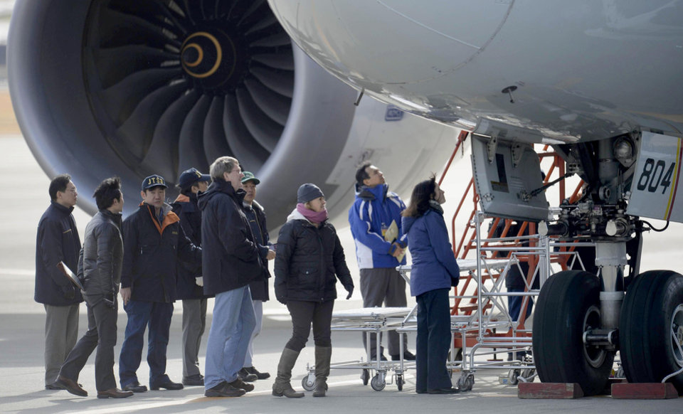U.S. officials, center,  inspect a All Nippon Airways jet which made an emergency landing Wednesday, at Takamatsu airport in Takamatsu, western Japan, Friday, Jan. 18, 2013. An official with Japan�s transport safety board says four U.S. officials, including two Boeing Co. representatives, have arrived at the airport in western Japan to inspect the troubled Boeing 787 jet. (AP Photo/Kyodo News)  JAPAN OUT, MANDATORY CREDIT, NO LICENSING IN CHINA, HONG KONG, JAPAN, SOUTH KOREA AND FRANCE