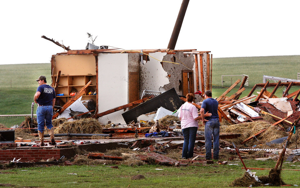Photo - Kiley Witte, 34, far right, is comforted by a  woman as they look at what remains  of his home on SH 74 east of Cashion after a tornado destroyed it  Tuesday afternoon,  May 24, 2011,   Witte and his dog were in a storm cellar in his front yard.  His wife and young son had done to Oklahoma City and were in a safe room of a business where she works.  Photo by Jim Beckel, The Oklahoman