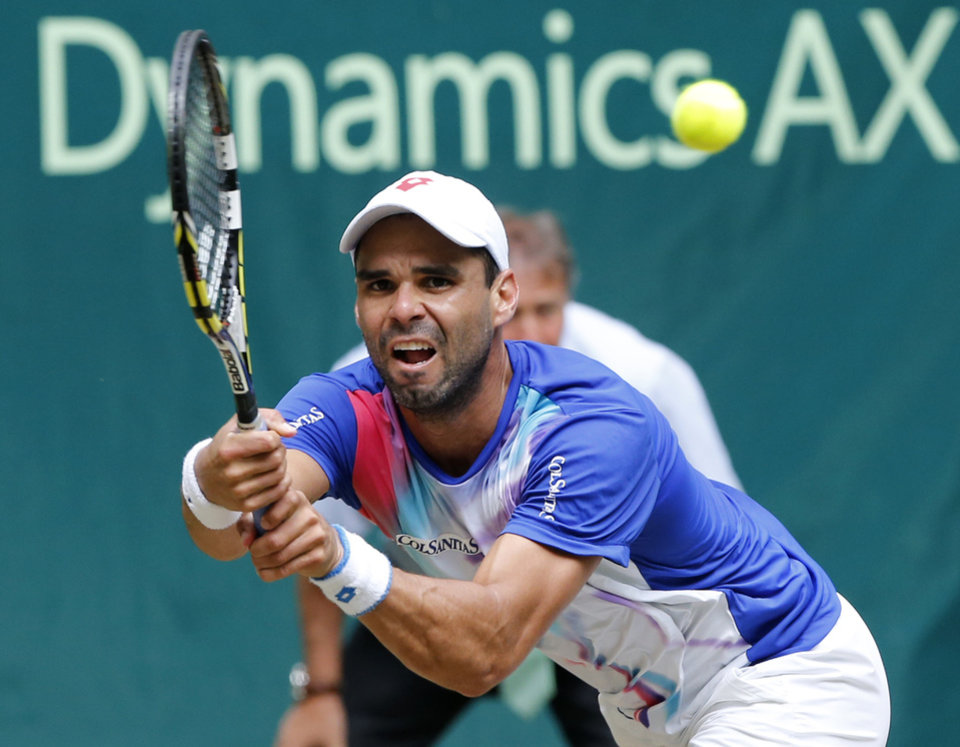 Photo - Colombia's Alejandro Falla returns the ball to Germany's Philipp Kohlschreiber during the semifinal match of the the Gerry Weber Open tennis tournament in Halle, Germany, Saturday, June 14, 2014. Falla won the match with 5-7, 7-6, 6-4. (AP Photo/Michael Probst)