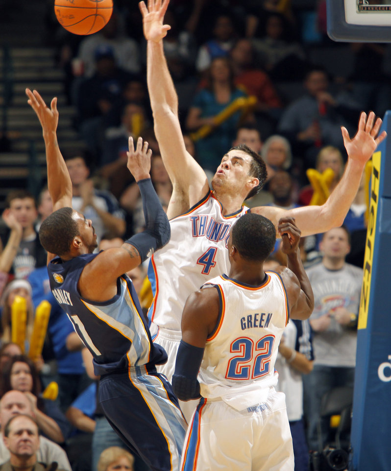 The Thunder's Nick Collison (4) tries to block the shot of Memphis' Mike Conley (11) during the NBA basketball game between the Oklahoma City Thunder and the Memphis Grizzlies at the Oklahoma City Arena on Tuesday, Feb. 8, 2011, Oklahoma City, Okla.