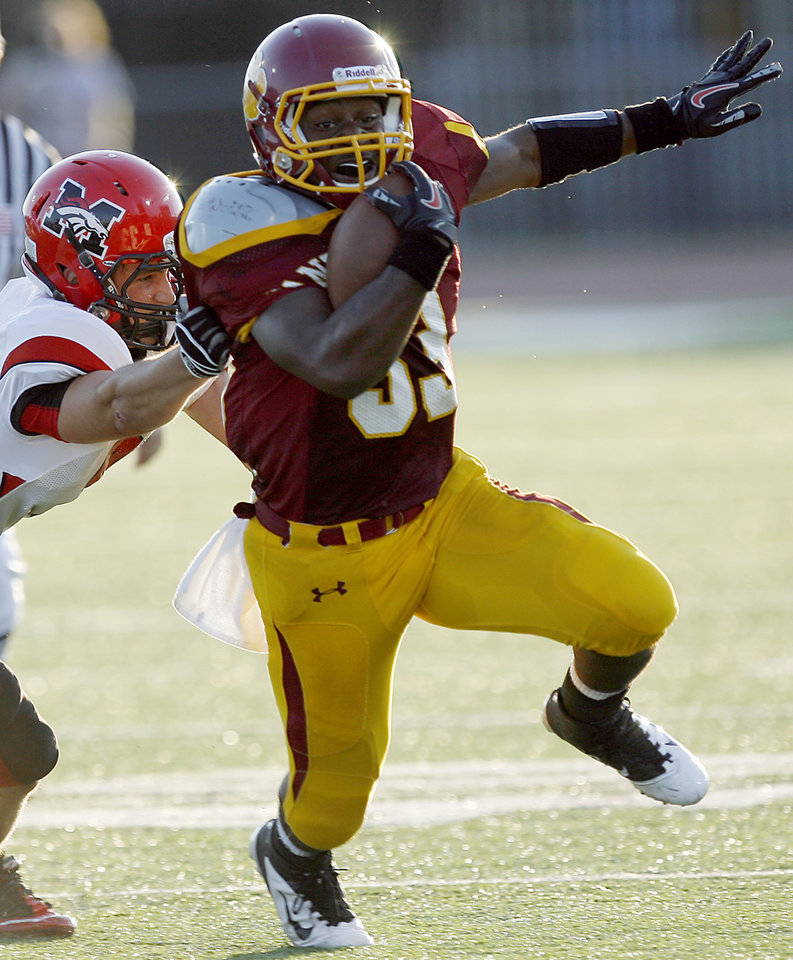 Putnam City North\'s Dre Holman tries to get away from Mustang\'s Steven Fruit during their high school football game at Putnam City Stadium in Oklahoma City on Thursday, September 8, 2011. Photo by John Clanton, The Oklahoman