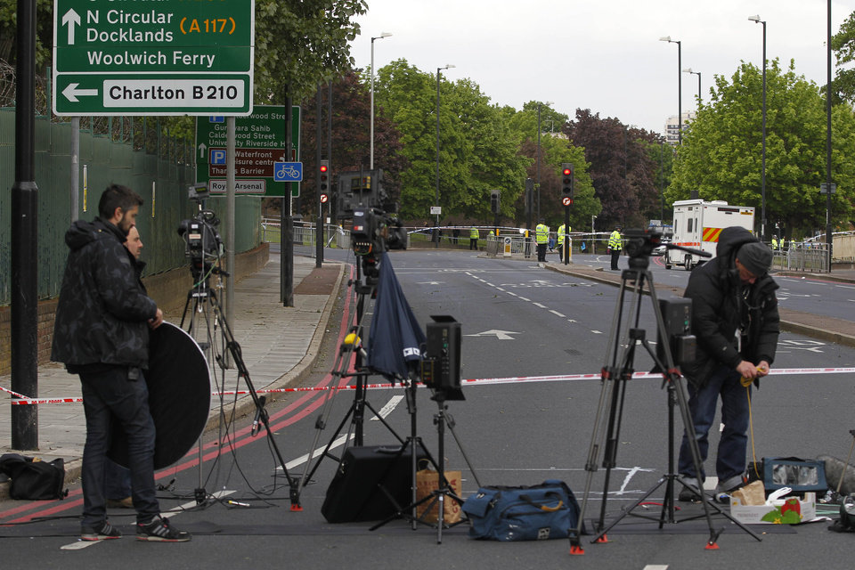 Photo - Media gather at the scene of a terror attack in Woolwich, southeast London, Thursday, May 23, 2013. A member of armed forces was attacked and killed by two men on Wednesday. (AP Photo/Sang Tan)