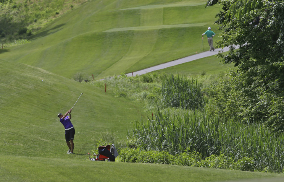 Photo - Katherine Kirk, of New Zealand, hits out of the fringe on the fourth hole during the final round of the Kingsmill Championship golf tournament at the Kingsmill resort  in Williamsburg, Va., Sunday, May 18, 2014.   (AP Photo/Steve Helber)
