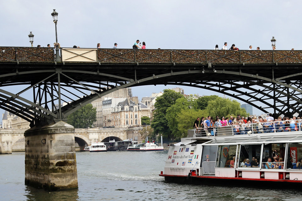 Photo - A wooden repaired section is seen, at top left, on the Pont des Arts bridge after a chunk of fencing with thousands of locks fell off under their weight in Paris, Monday, June 9, 2014. The thousands of locks that cling like barnacles to the Pont des Arts in Paris have become a symbol of danger, rather than love, after a chunk of fencing fell off under their weight. The fencing tumbled late Sunday on the pedestrian bridge, which crosses the Seine. (AP Photo/Francois Mori)