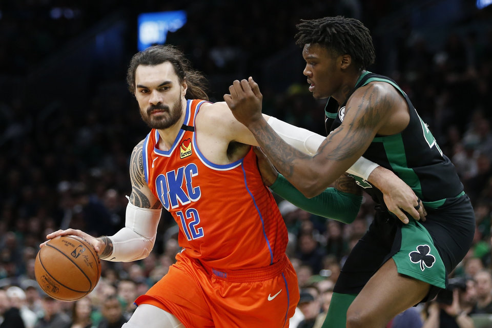 Photo - Oklahoma City Thunder's Steven Adams (12) drives past Boston Celtics' Robert Williams III during the second half of an NBA basketball game, Sunday, March, 8, 2020, in Boston. (AP Photo/Michael Dwyer)