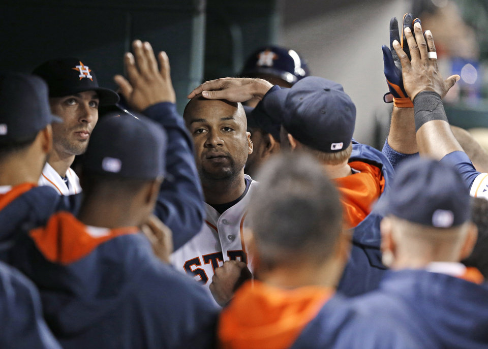 Photo - Houston Astros' Carlos Corporan, center, is congratulated in the dugout after hitting a solo home run against the Kansas City Royals in the fifth inning of a baseball game Tuesday, April 15, 2014, in Houston. (AP Photo/Pat Sullivan)