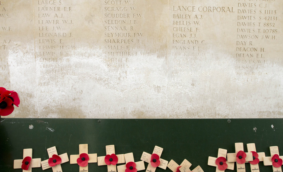 Photo - Wooden crosses with paper poppies are seen in front of a damaged  stone wall with names of missing WWI solders on it at the Menin Gate in Ypres, Belgium on Monday, April 15, 2013. Commonwealth cemeteries and monuments around the world are currently being renovated in preparation for centenary events which begin in 2014. At the Menin Gate, work has already begun on replacing damaged stone panels with newly engraved panels. (AP Photo/Virginia Mayo)